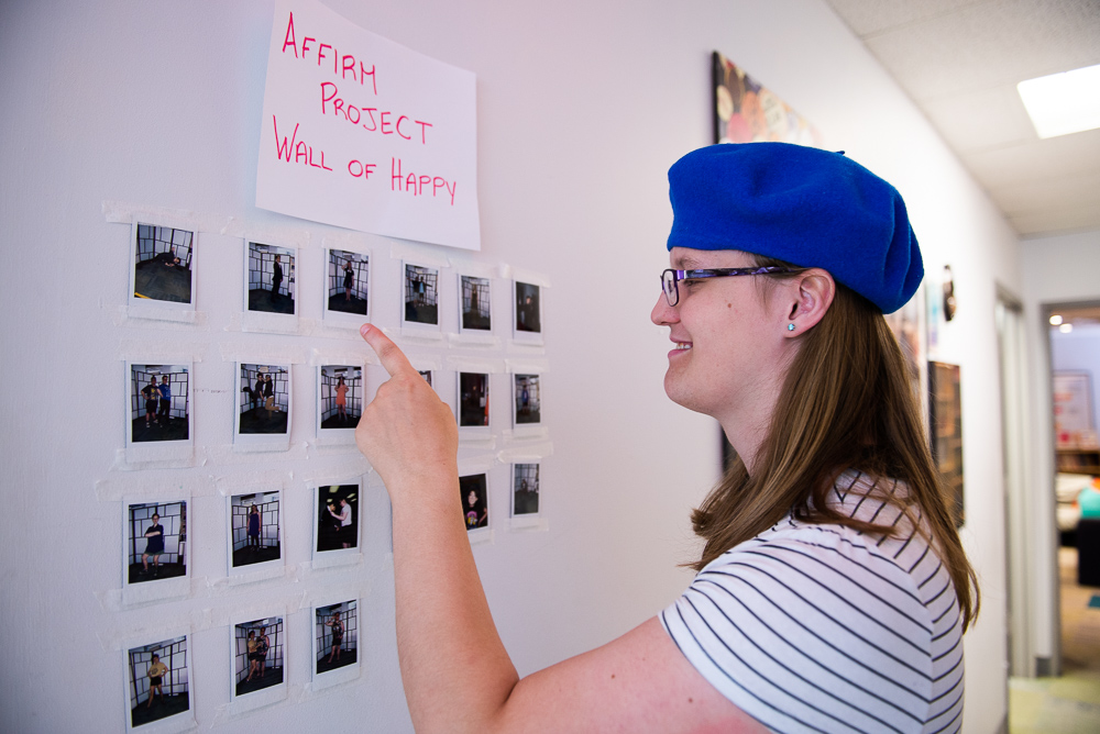 Penelope next to the 'Wall of Happy', pointing at a photo of her in her new clothes, thanks to Affirm Project.