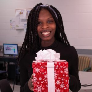 A photo of Raquel holding a gift.