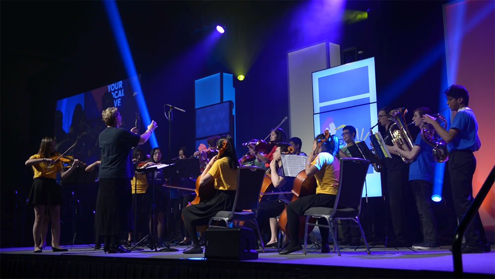 A photo of an orchestra on stage at the CBYA Gala.