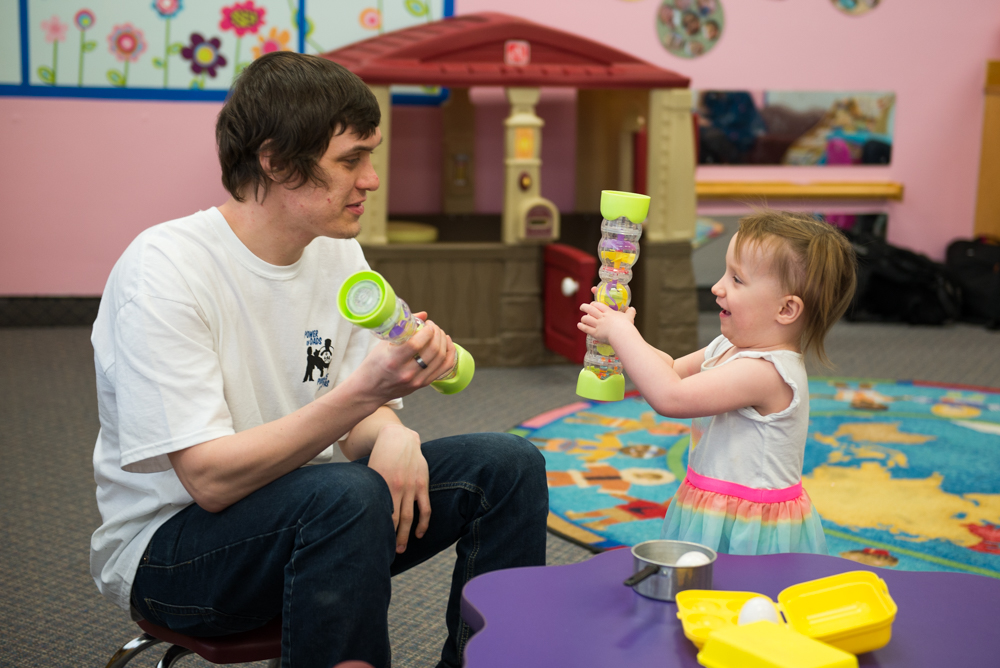 A photo of Myke playing with his daughter.