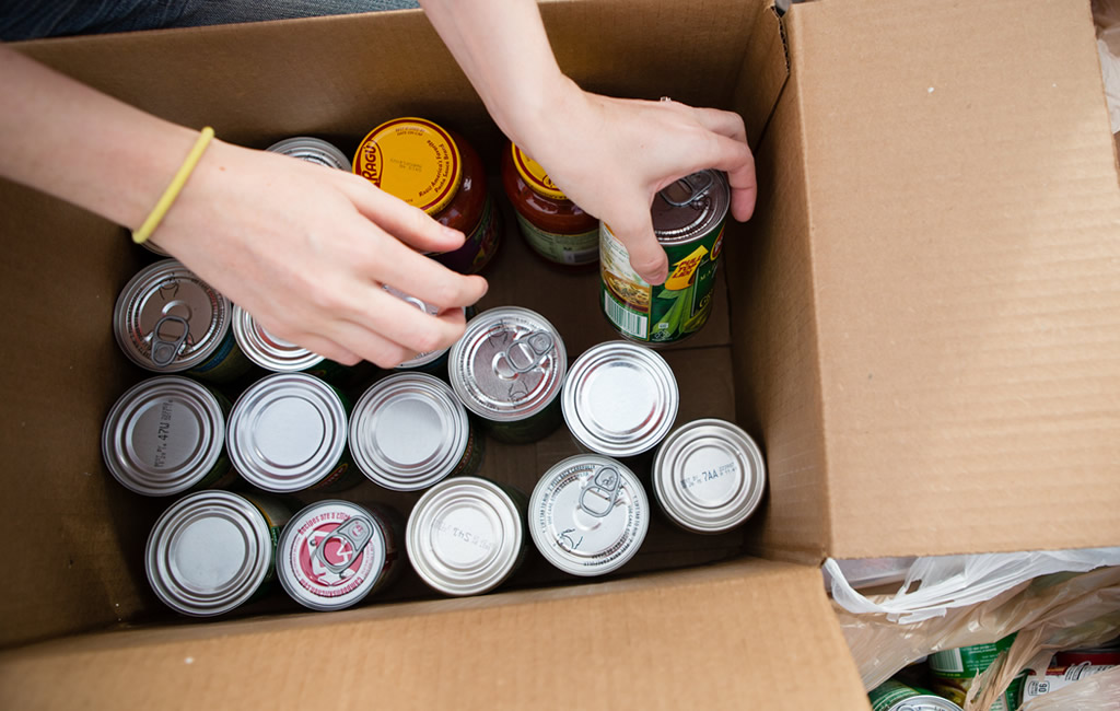 A woman filling a box with canned goods.