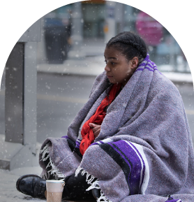 A homeless youth begging for money on the street in the snow.