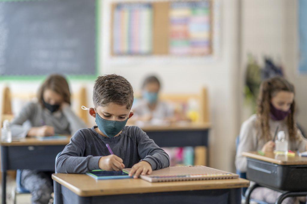 Des étudiants qui portent un masque en classe
