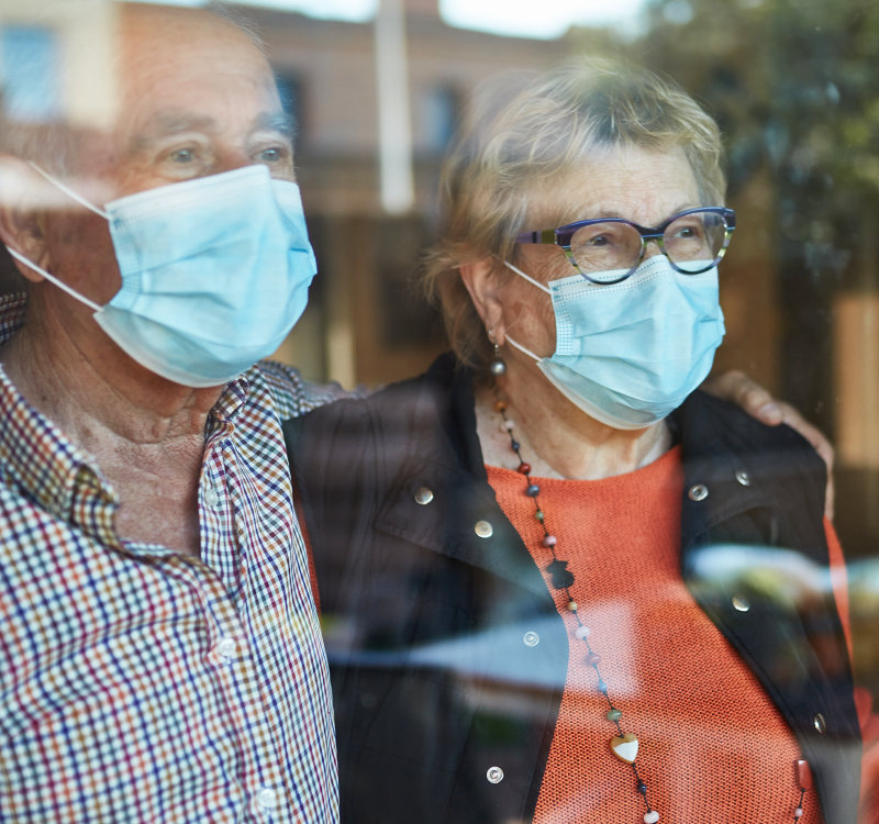 A grandmother and grandfather standing in a window wearing masks to protect them and others from COVID-19.