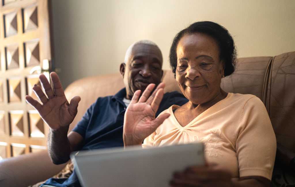 A couple sitting on the couch waving to someone on their tablet.
