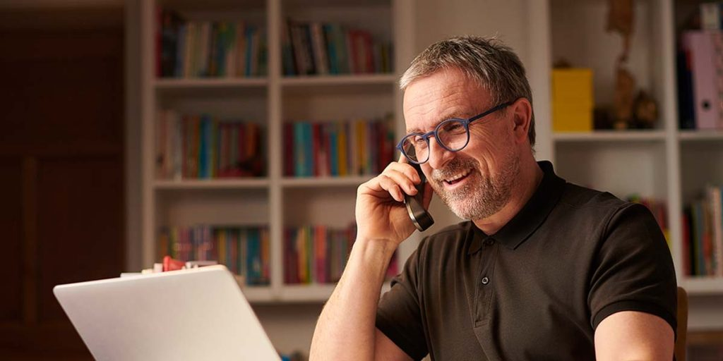 A photo of a man in a home office talking on the phone sitting in front of his laptop.