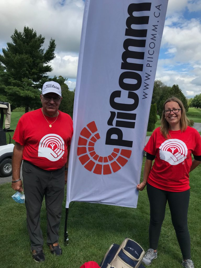 Two people in United Way t-shirts standing with a PiiComm sign.